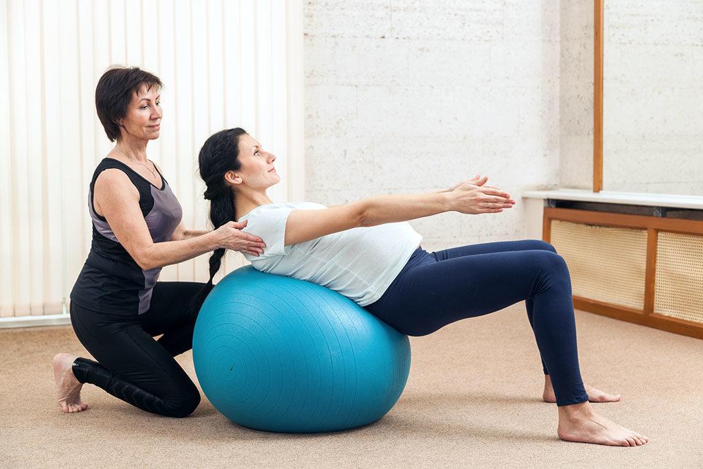 Gestante em sessão de fisioterapia fazendo exercício na bola de pilates