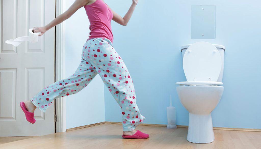 Mulher corre para a privada do banheiro com papel higiênico na mão
