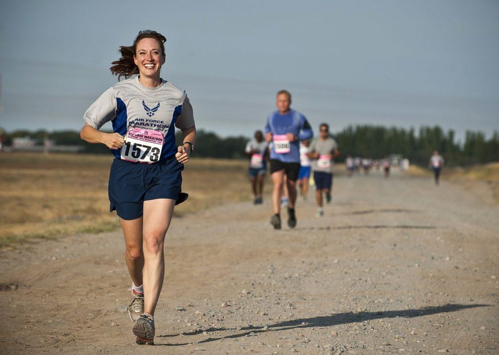 Mulher correndo numa competição em uma estrada de terra