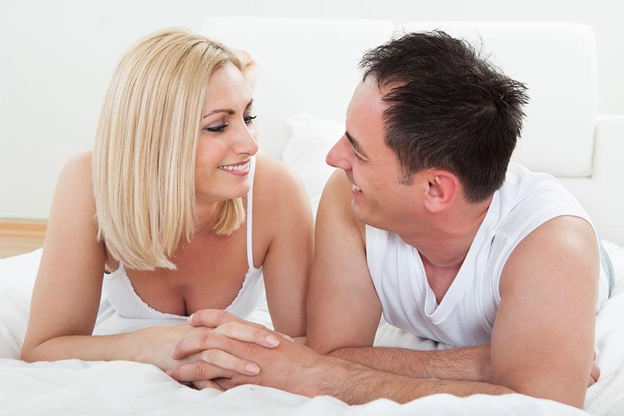 Casal feliz na cama de mãos dadas