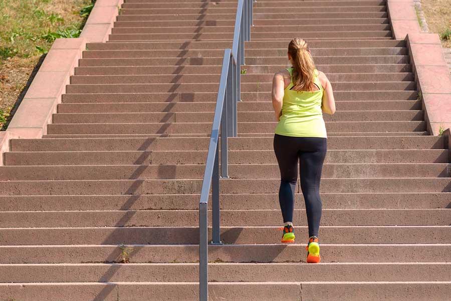 Mulher adulta subindo uma escadaria