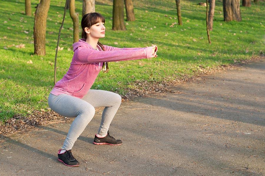 Mulher adulta em posição de agachamento no parque