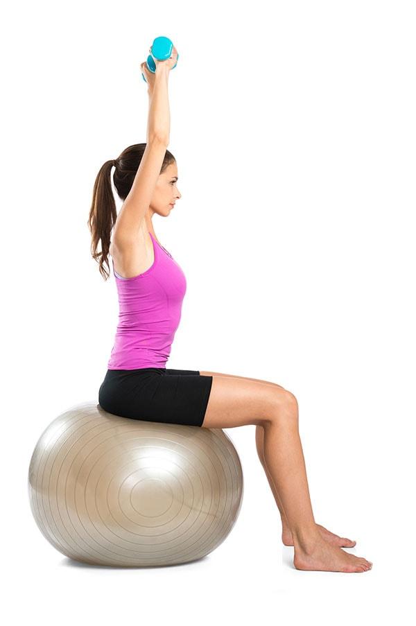 Mulher se alonga com pesos nas mãos sobre uma bola de pilates