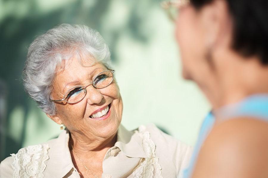 Senhora sorrindo conversa com alguém